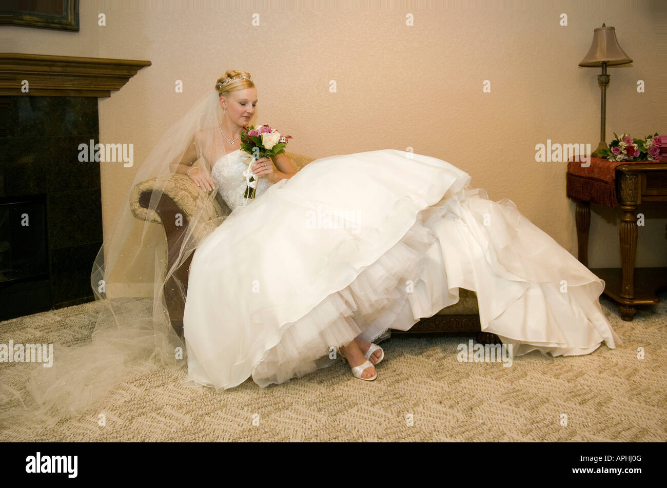 bride lounging or waiting before the wedding in chaise sofa couch full body portrait 'getting ready shots' - Stock Image