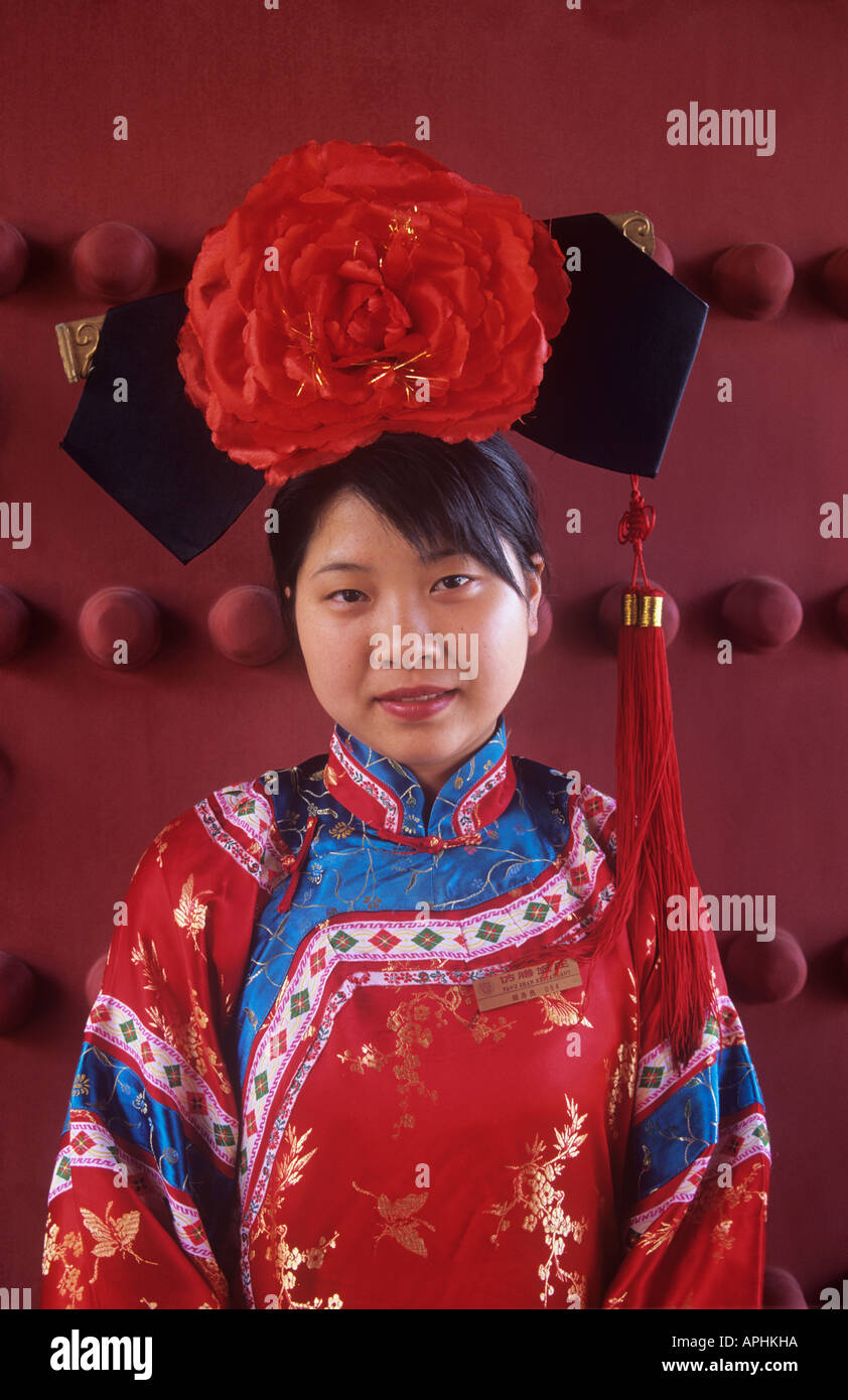 Waitress with a huge red rose headdress and very colourful costume at the Fangshan Restaurant Fangshan means that the foods provided in this restaurant imitate those that were cooked in the court kitchen This restaurant was opened in 1925 by a worker that worked in the palace storeroom That worker invited some cooks that worked in the kitchen in the Qing court to work together with him in Beihai Park in Beijing - Stock Image