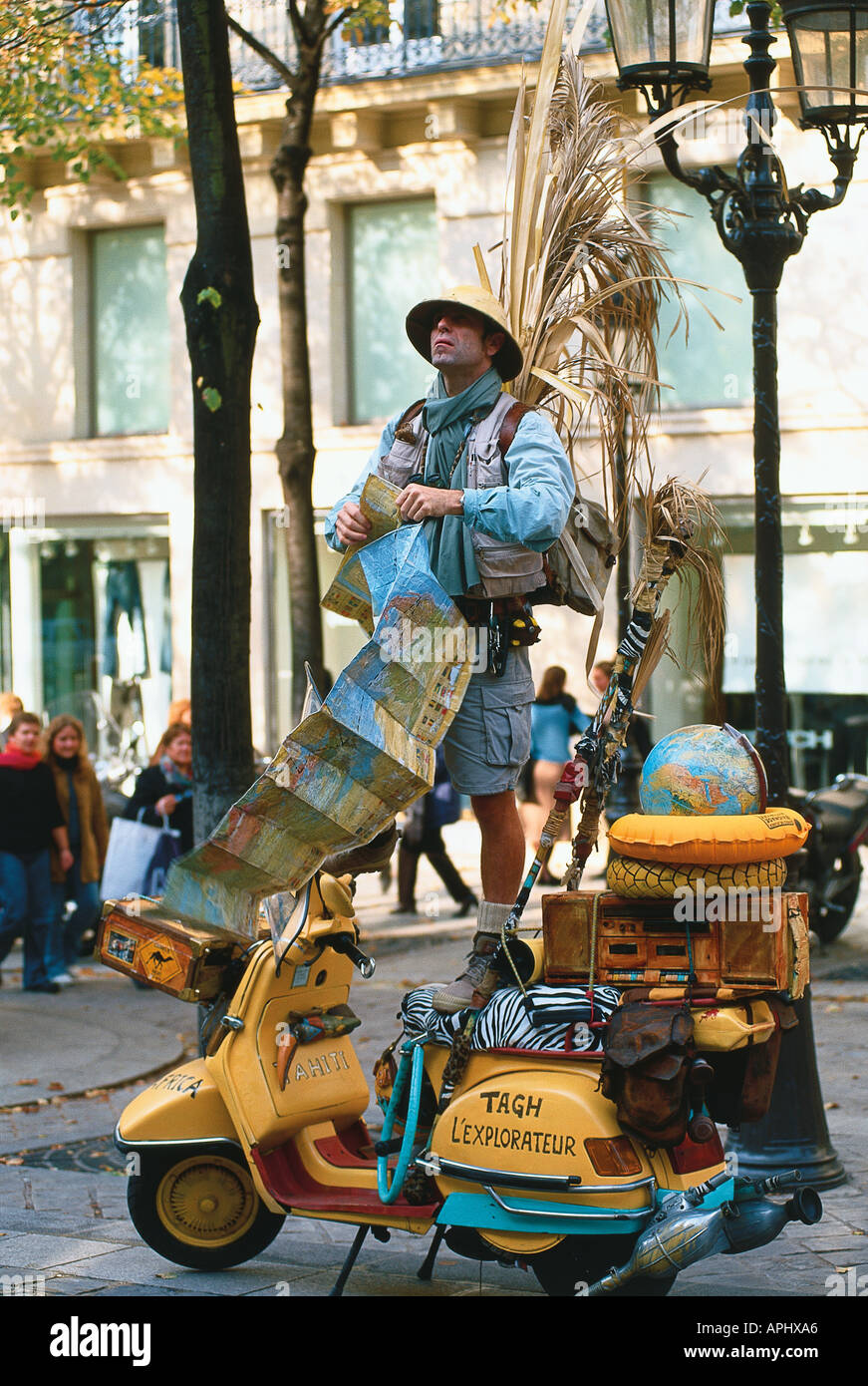 Place de la Sorbonne Paris France A mime artist dressed as an explorer holding a map moped in foreground world globe - Stock Image