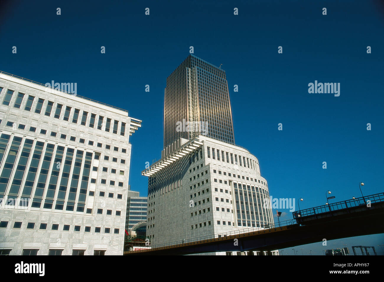 Modern buildings which house offices in city s Docklands developed in 1980s Canary Wharf tower Isle of Dogs London England - Stock Image