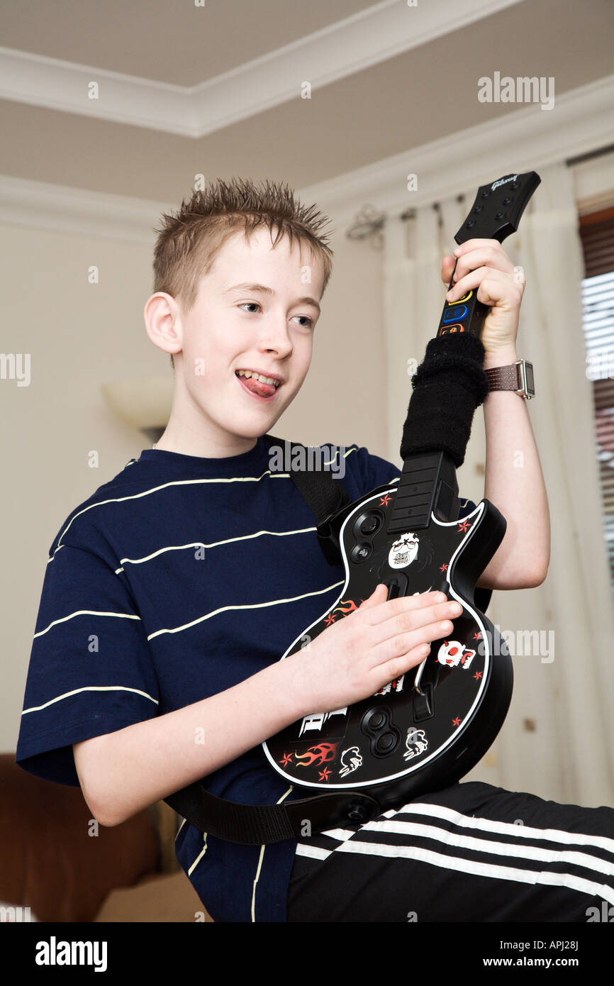 Youth playing Guitar Hero console game - Stock Image