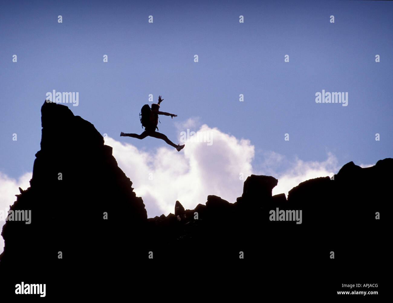 A climber leaps from rock pinnacle during a climb on a sunny day in rugged country - Stock Image