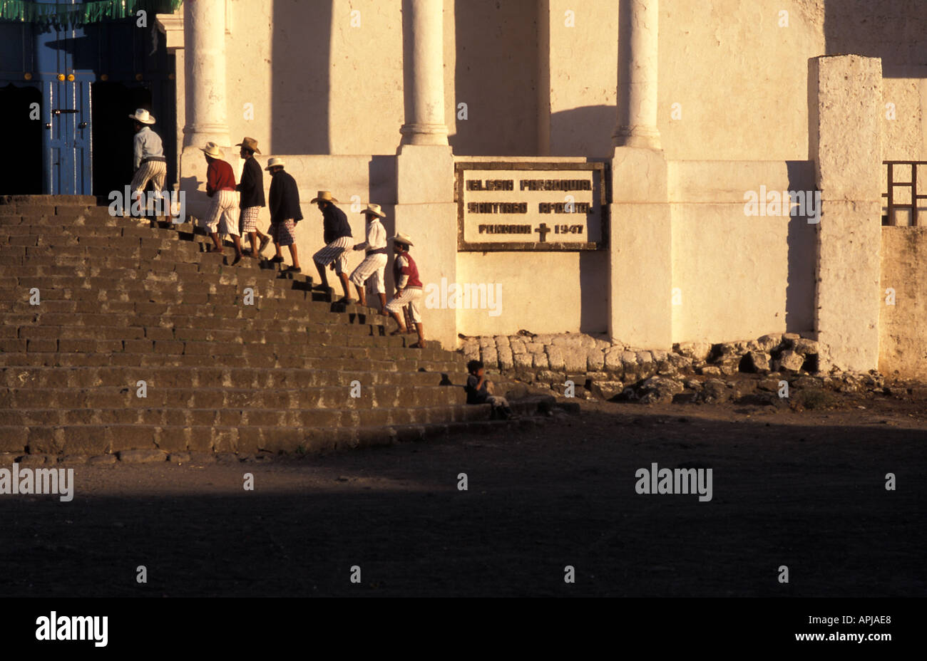 Group of religious elders ascending the steps of the colonial church at sunset Santiago Atitlan Dept Solola Guatemala - Stock Image