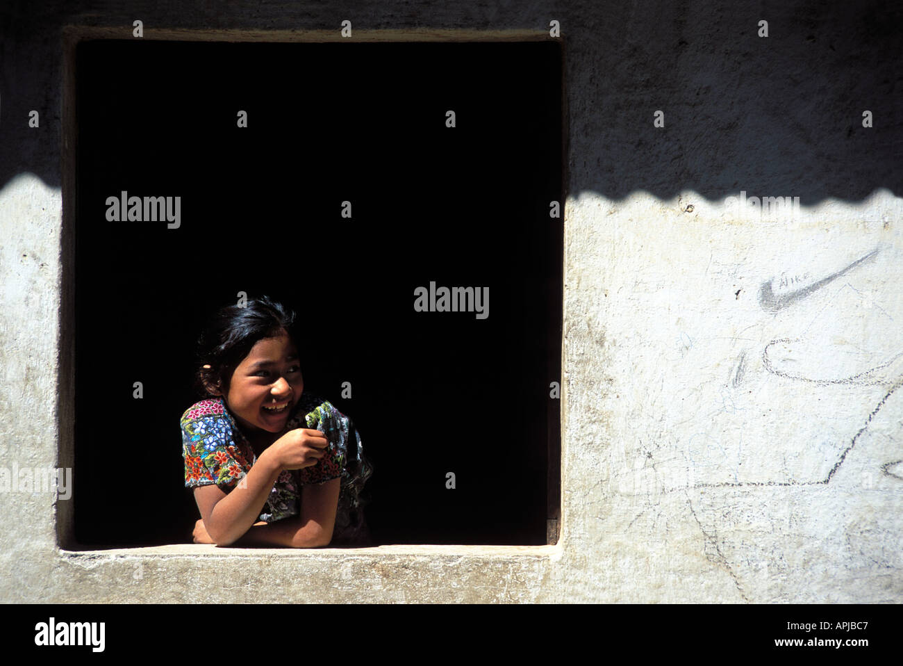 Maya girl in the window of their home Wearing traditional style attire Santiago Atitlan Lake Atitlan Dept Solola Guatemala - Stock Image