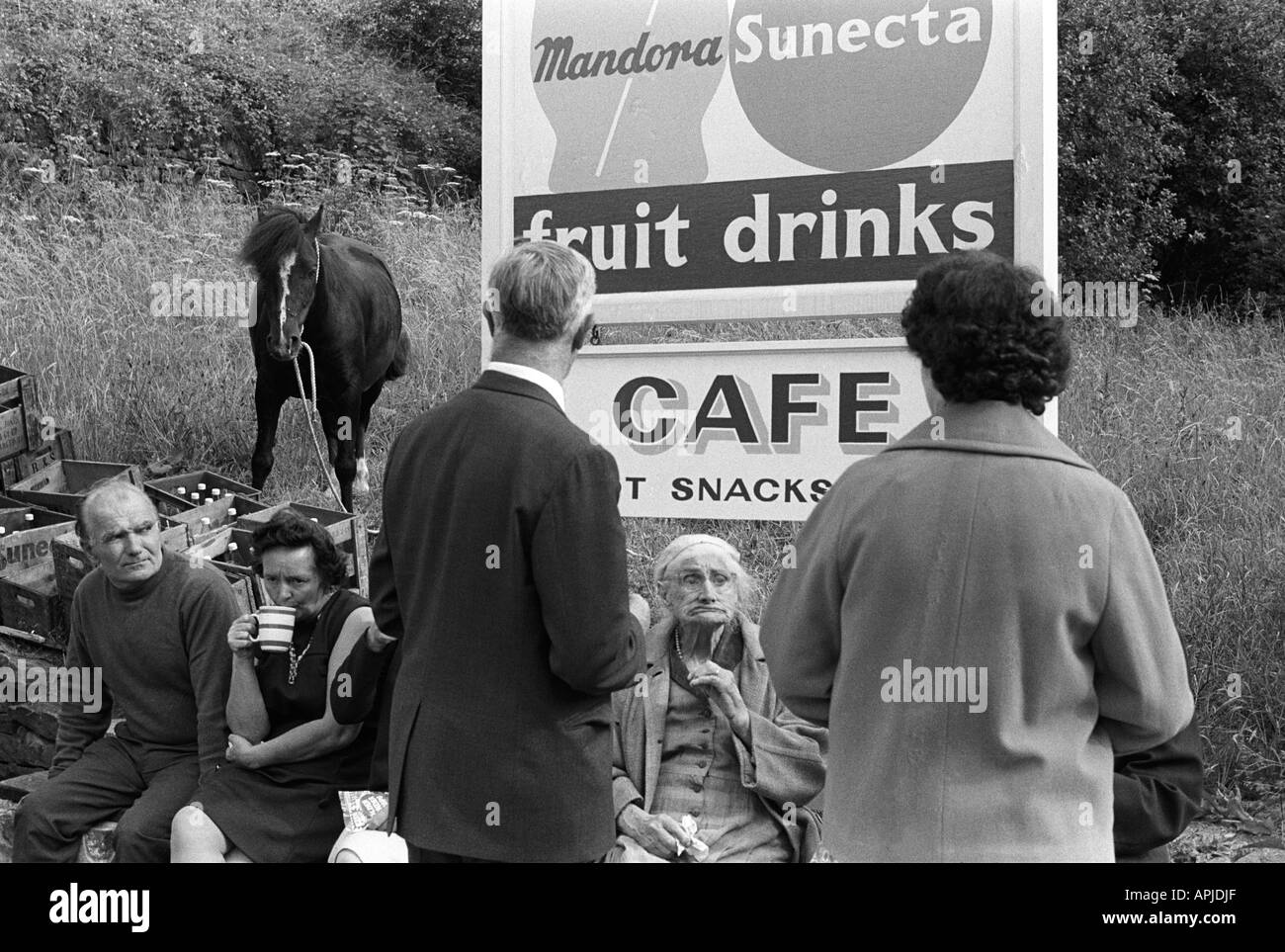 Family outing 1970s drinking a cup of tea under outside