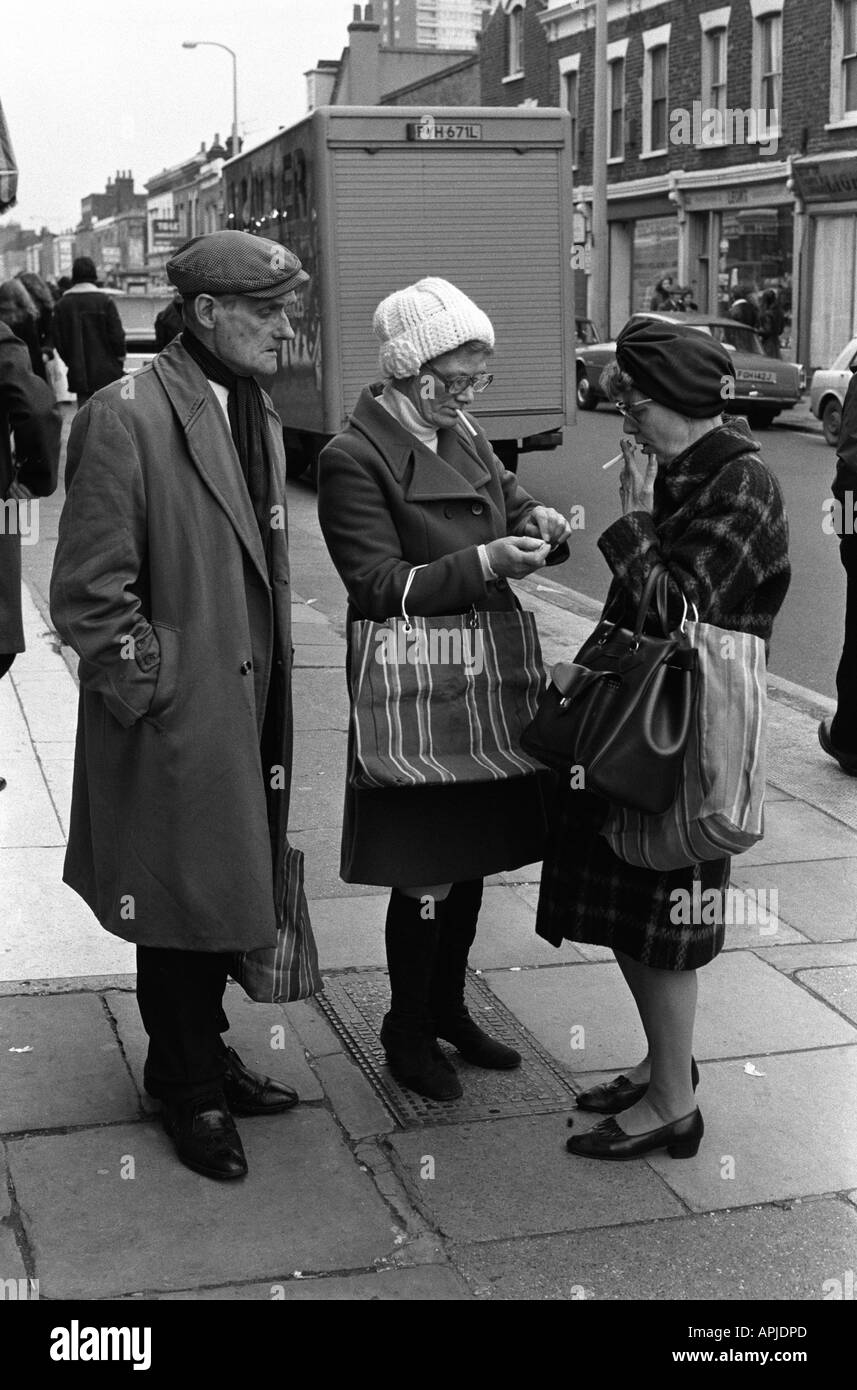 Working class couple friends 1970s Uk Lighting up smoking in the street. Roman Road East End of London England 70s England HOMER SYKES - Stock Image