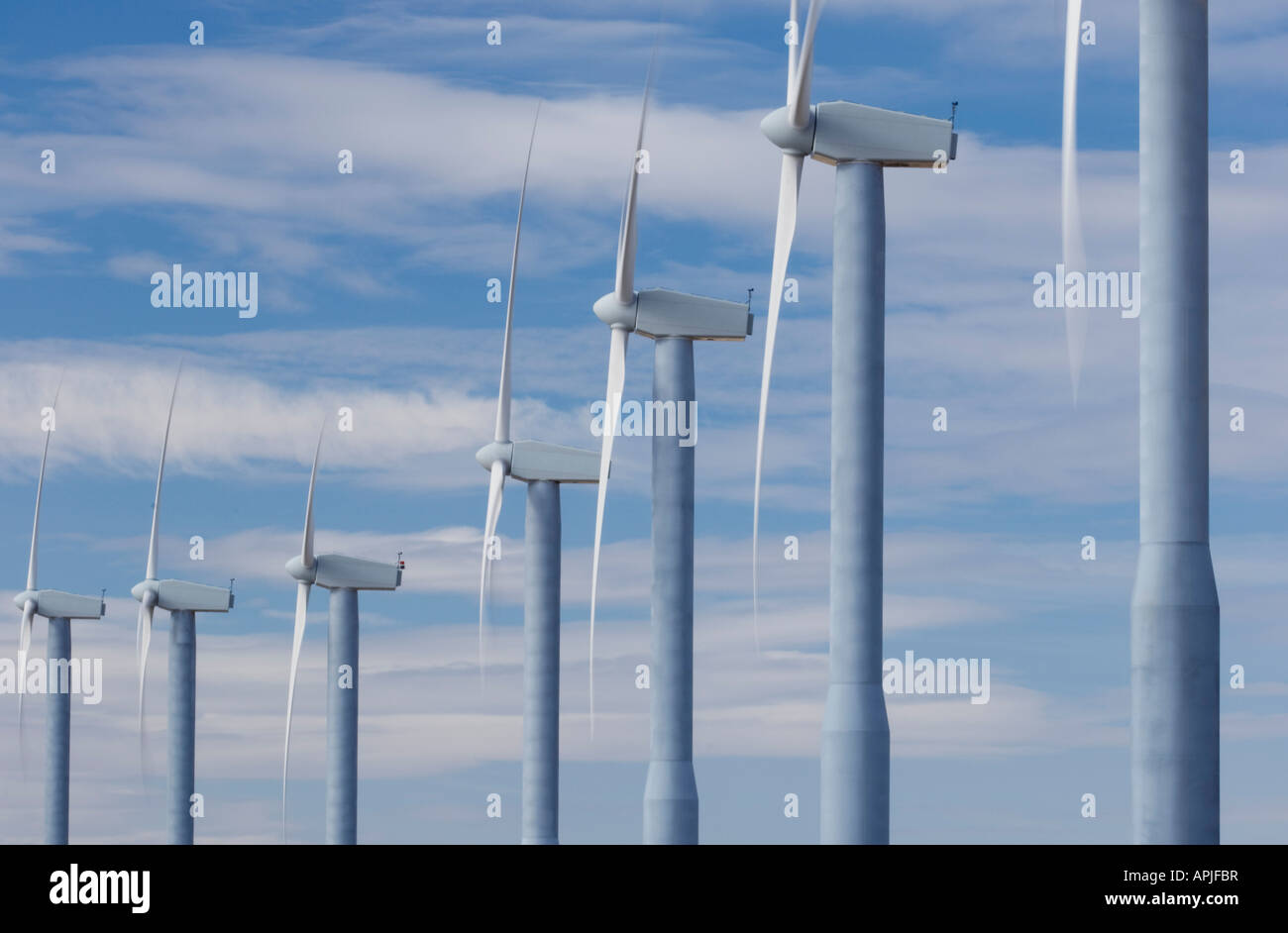 Propellers of windturbines spin against a sky of broken clouds - Stock Image