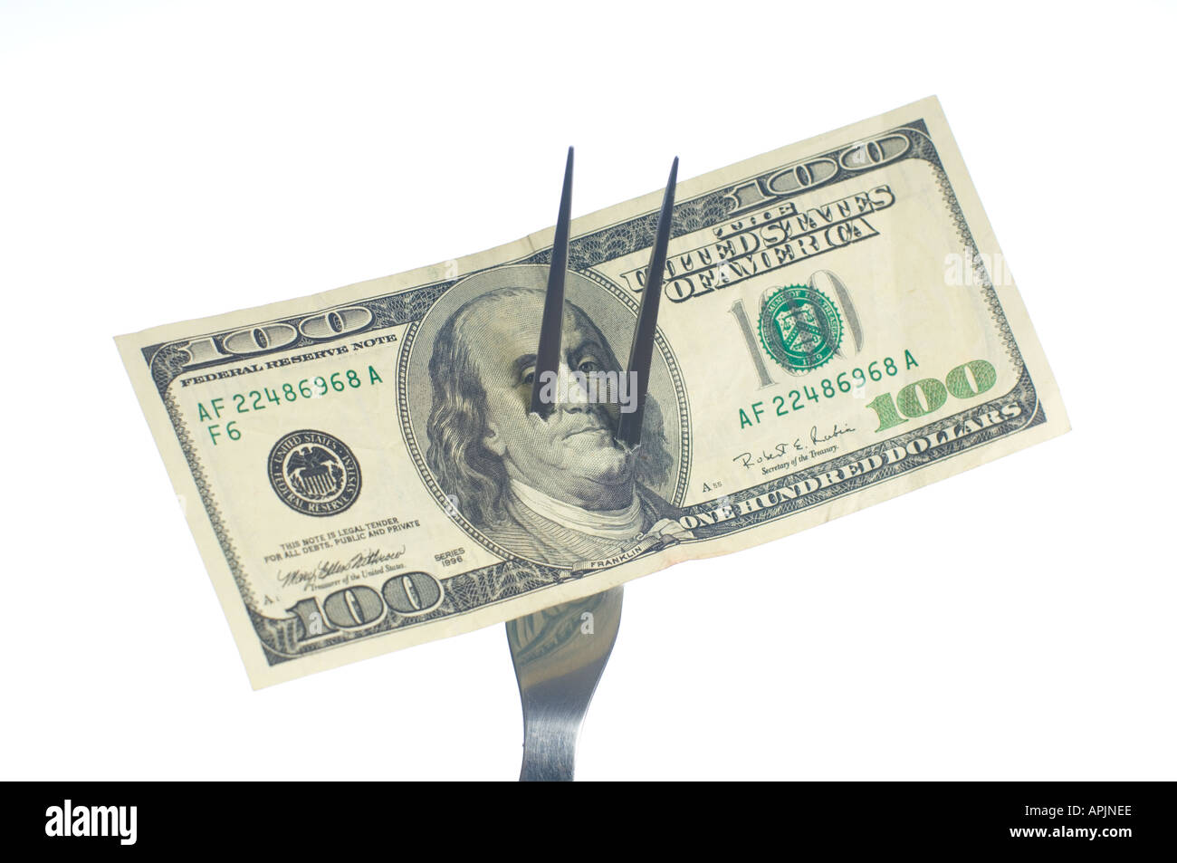 conceptual closeup of one hundred dollar bill US impaled on a sharp carving fork - Stock Image
