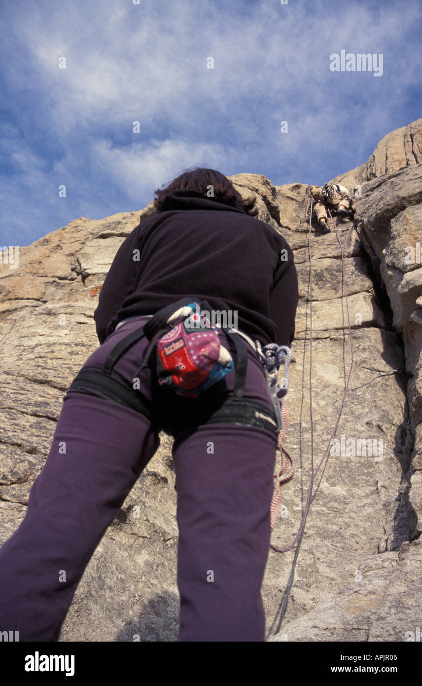 Idaho City of Rocks view from bellow female on belay with male climbing above - Stock Image