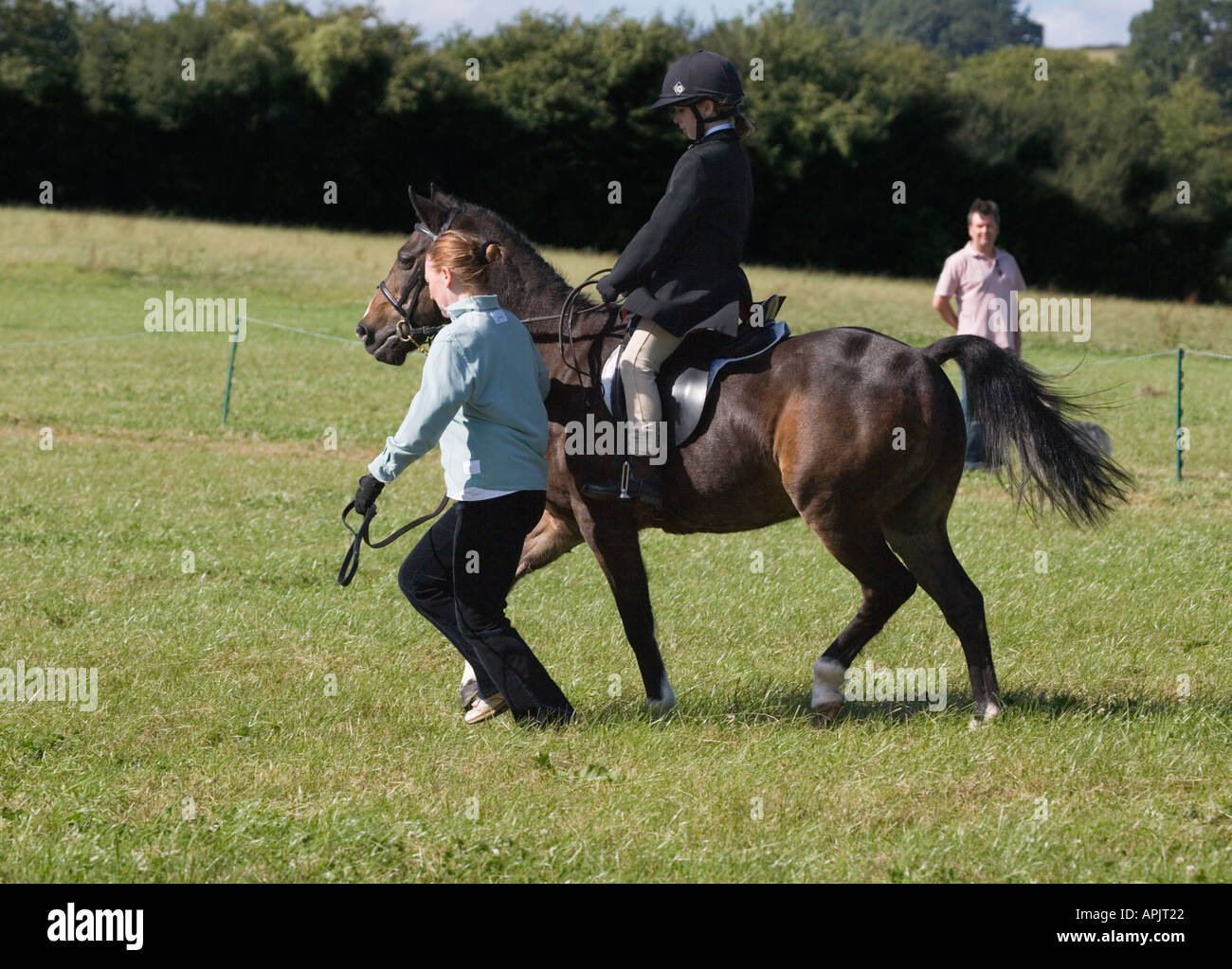 WOMAN RUNNING WITH LITTLE GIRL IN RIDING OUTFIT/ CLOTHES ON SMALL PONY AT EVENT IN UK Stock Photo