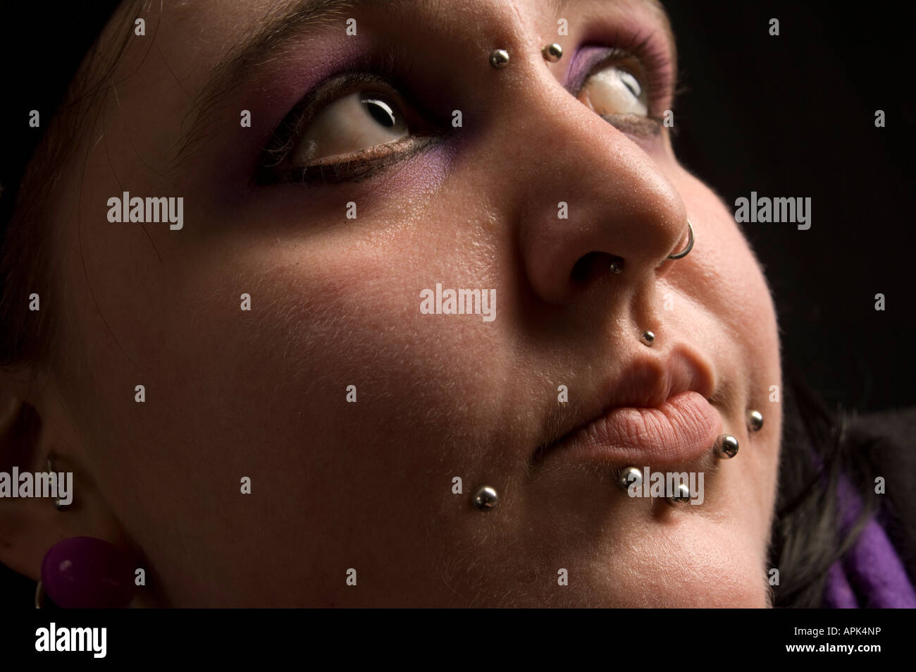 close up of the face of a young chubby welsh woman with multiple piercings in her nose and lips Stock Photo