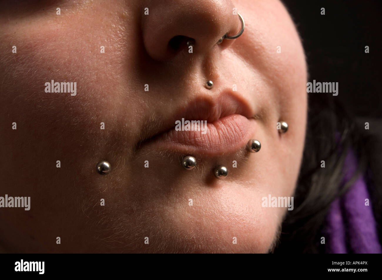 close up of the lips and chin of a young welsh woman with multiple facial piercings Stock Photo