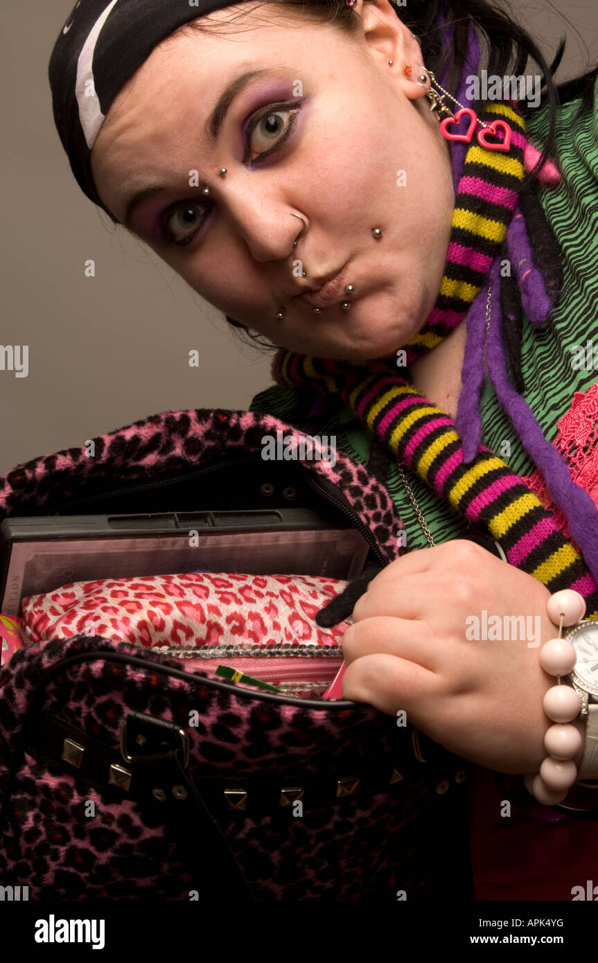 young chubby punk woman with pierced face showing the contents of her handbag Stock Photo