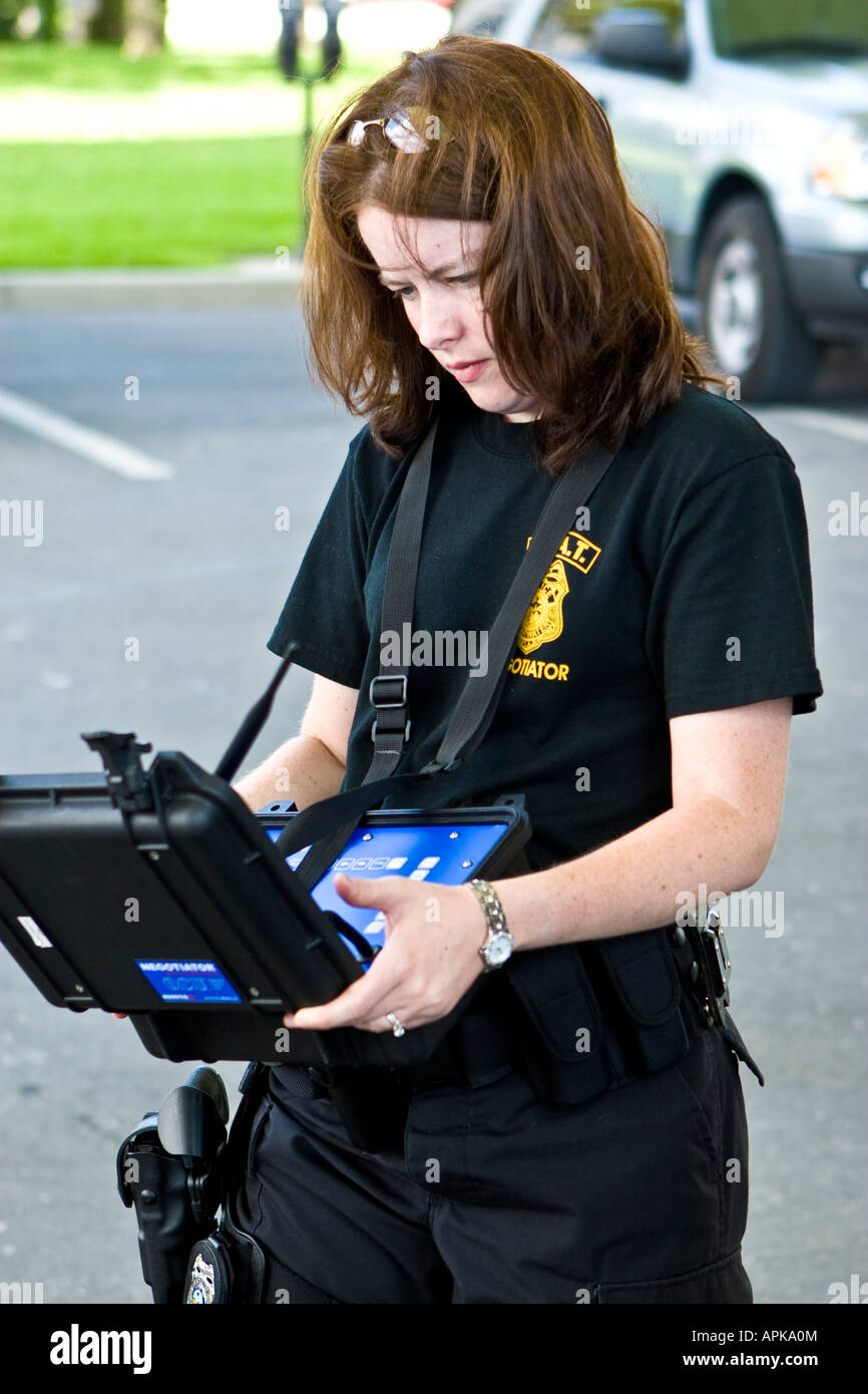 Female Police SWAT Negotiator Working on a Tactical Robot Control Box Stock Photo
