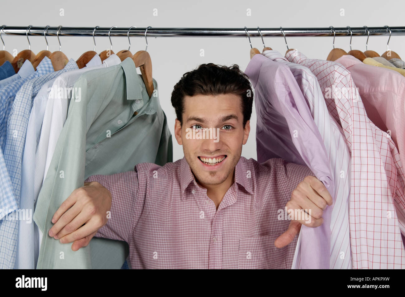 Young man with clothing rack - Stock Image