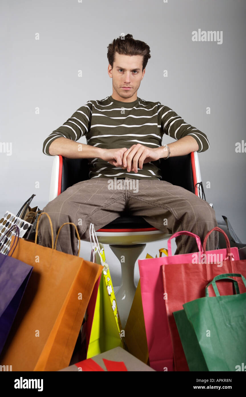 Tired young man with shopping bags - Stock Image