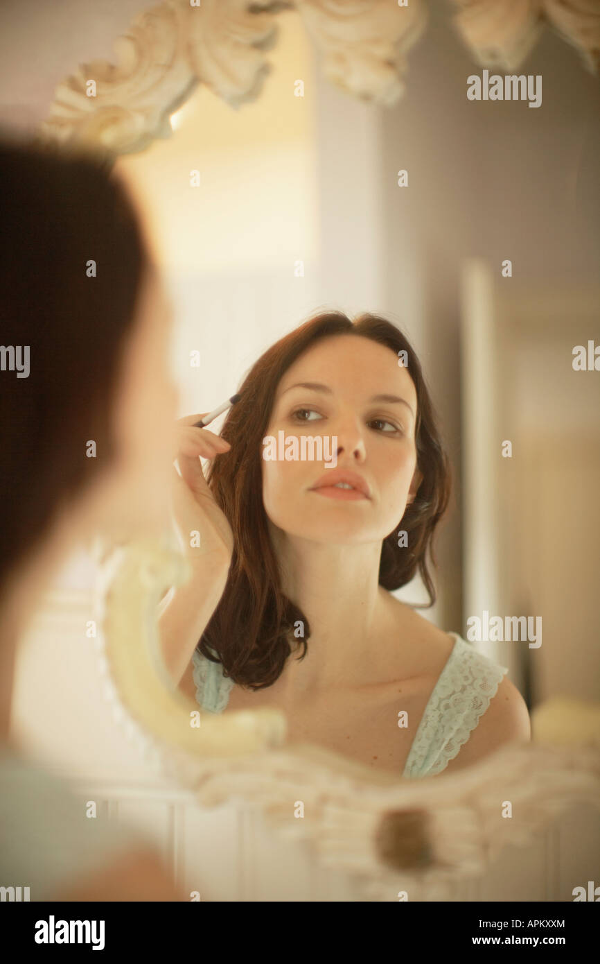 Woman applying make-up in front of mirror Stock Photo
