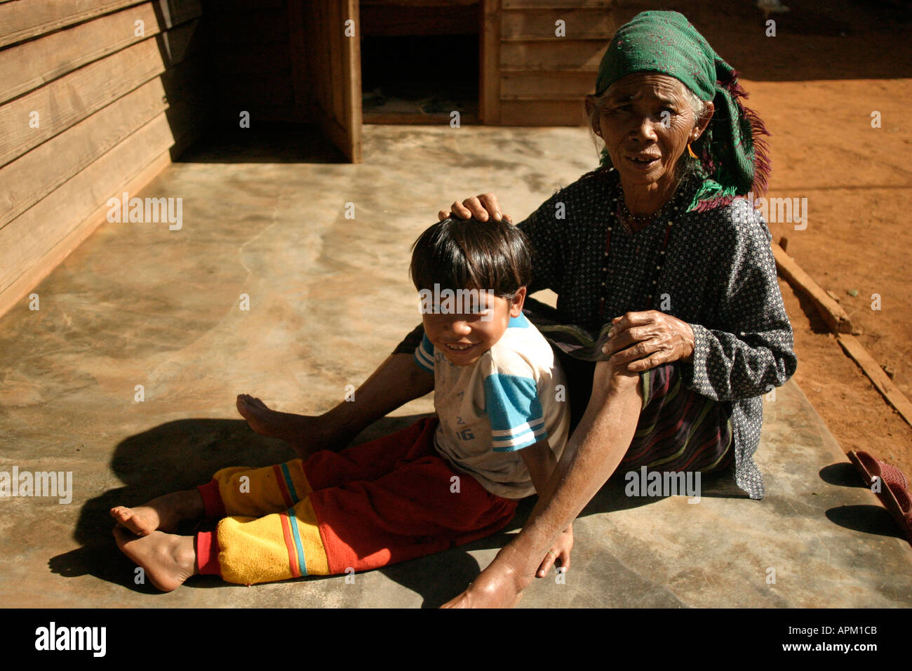 grandmother old woman looks through hair of small boy grandchild in the sun Stock Photo