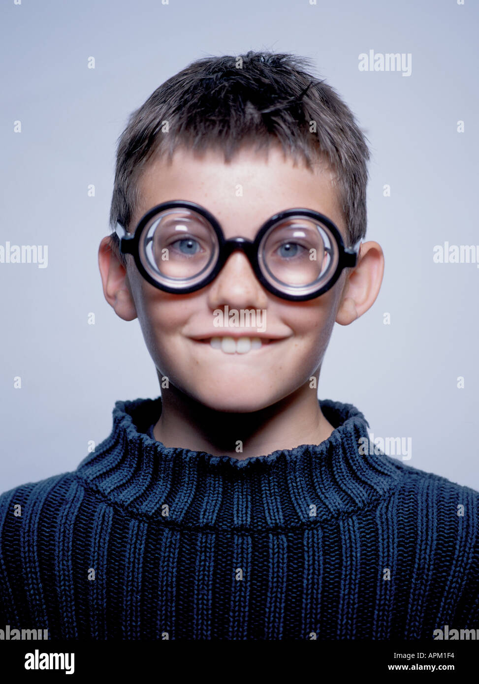 Portrait of a goofy young boy wearing thick glasses - Stock Image