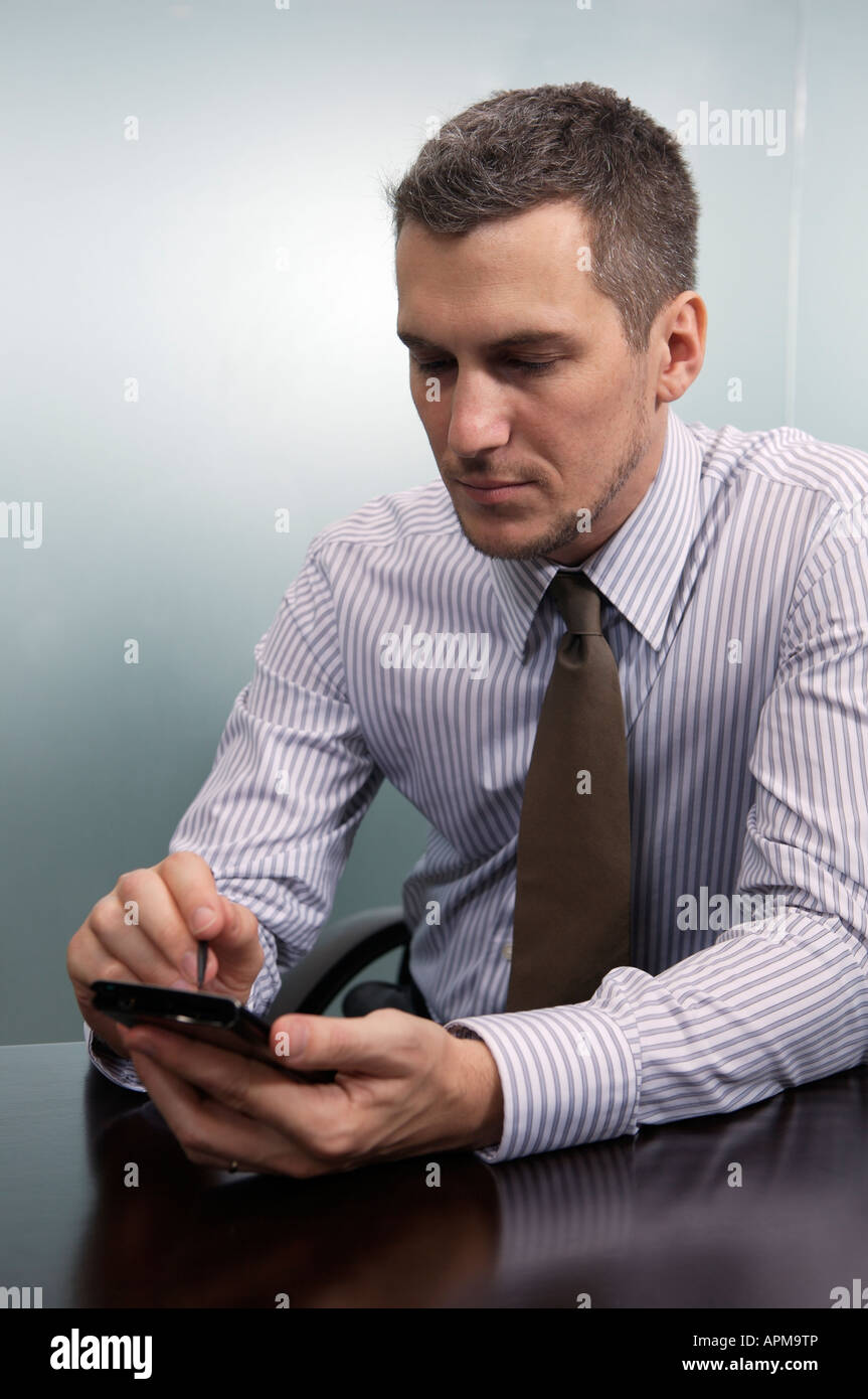 Businessman using electronic agenda in his office - Stock Image