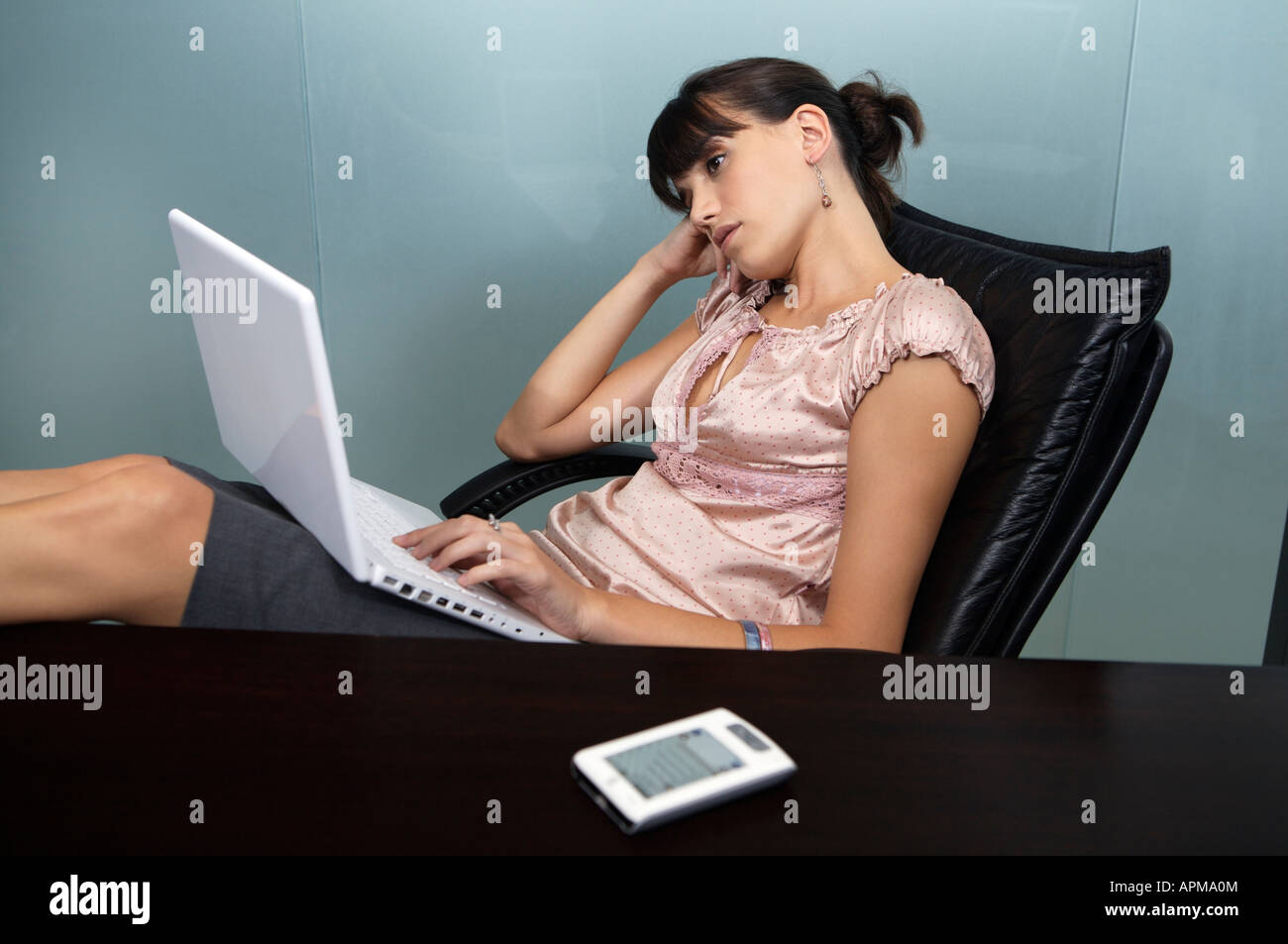 Business woman with her feet on the table using her notebook computer Stock Photo