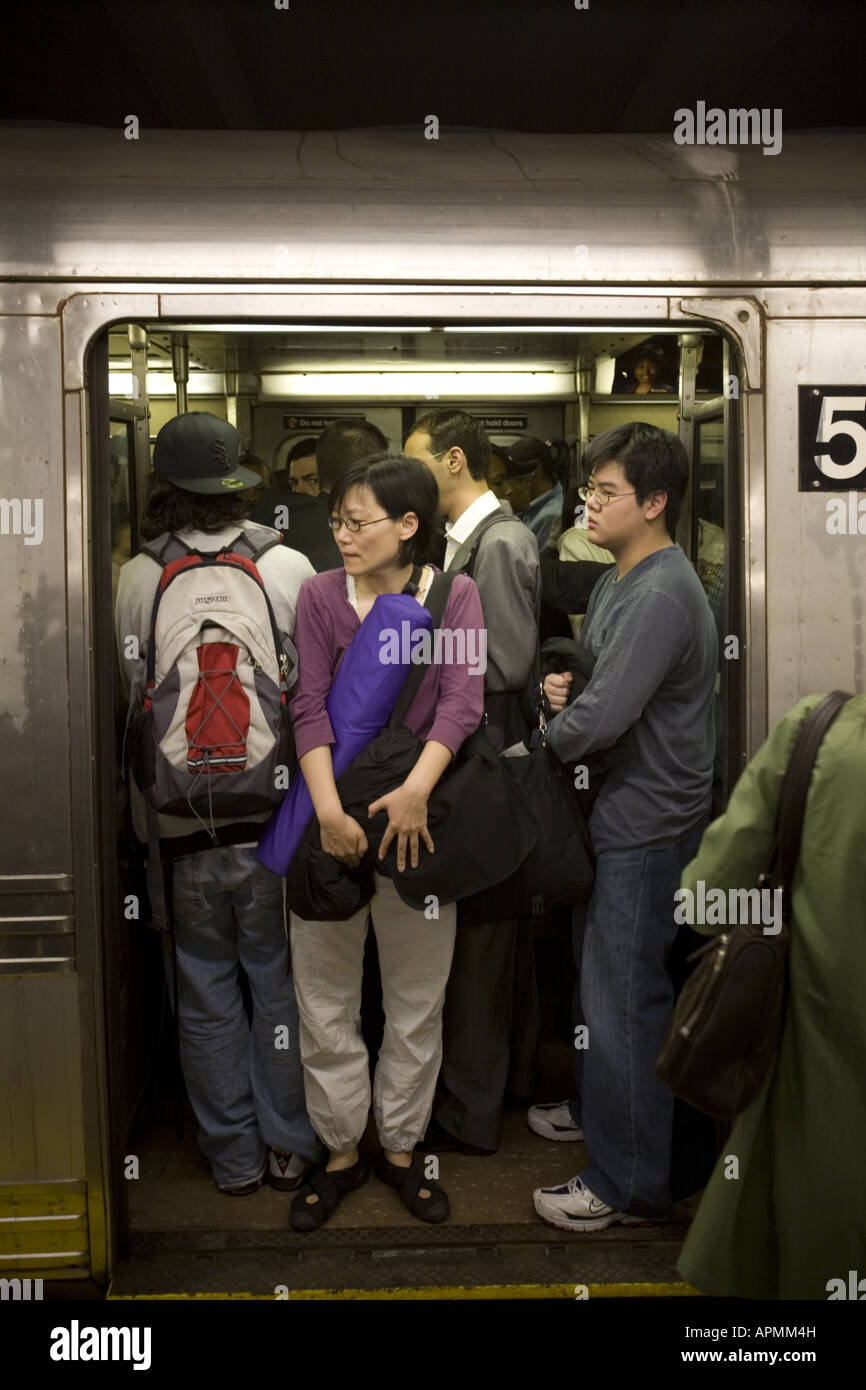 Crowded subway train at rush hour in New York City - Stock Image