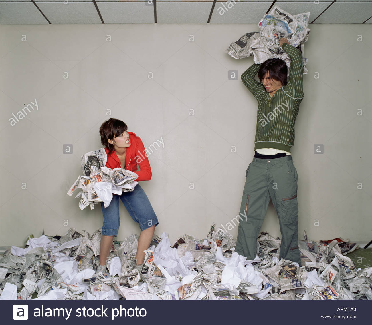 Two people playfighting with newspaper - Stock Image