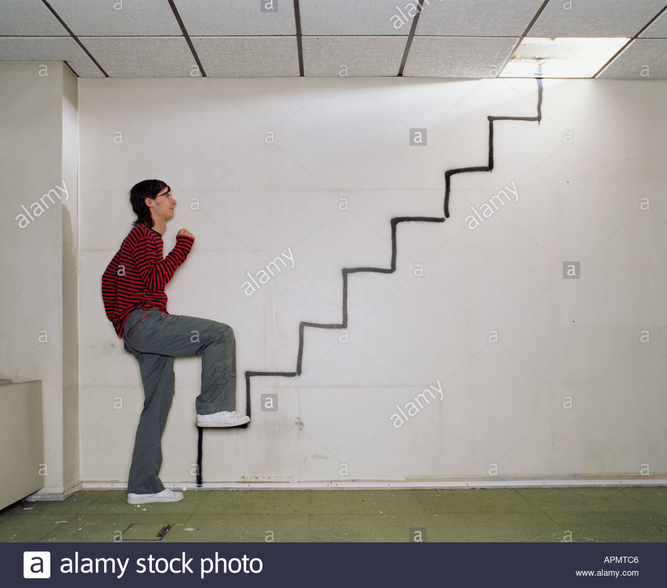 Man walking up a spray painted stairway - Stock Image