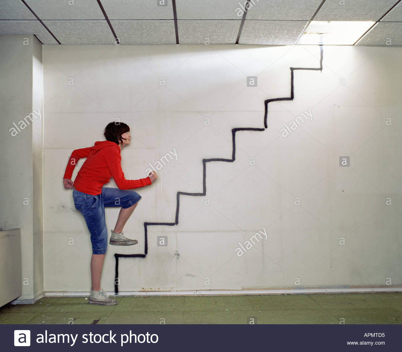 Woman walking up spray painted stairway - Stock Image