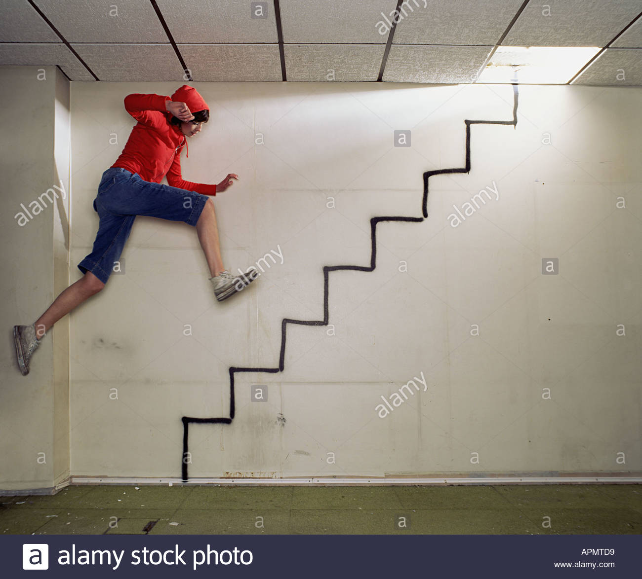 Woman jumping on spray painted stairway - Stock Image