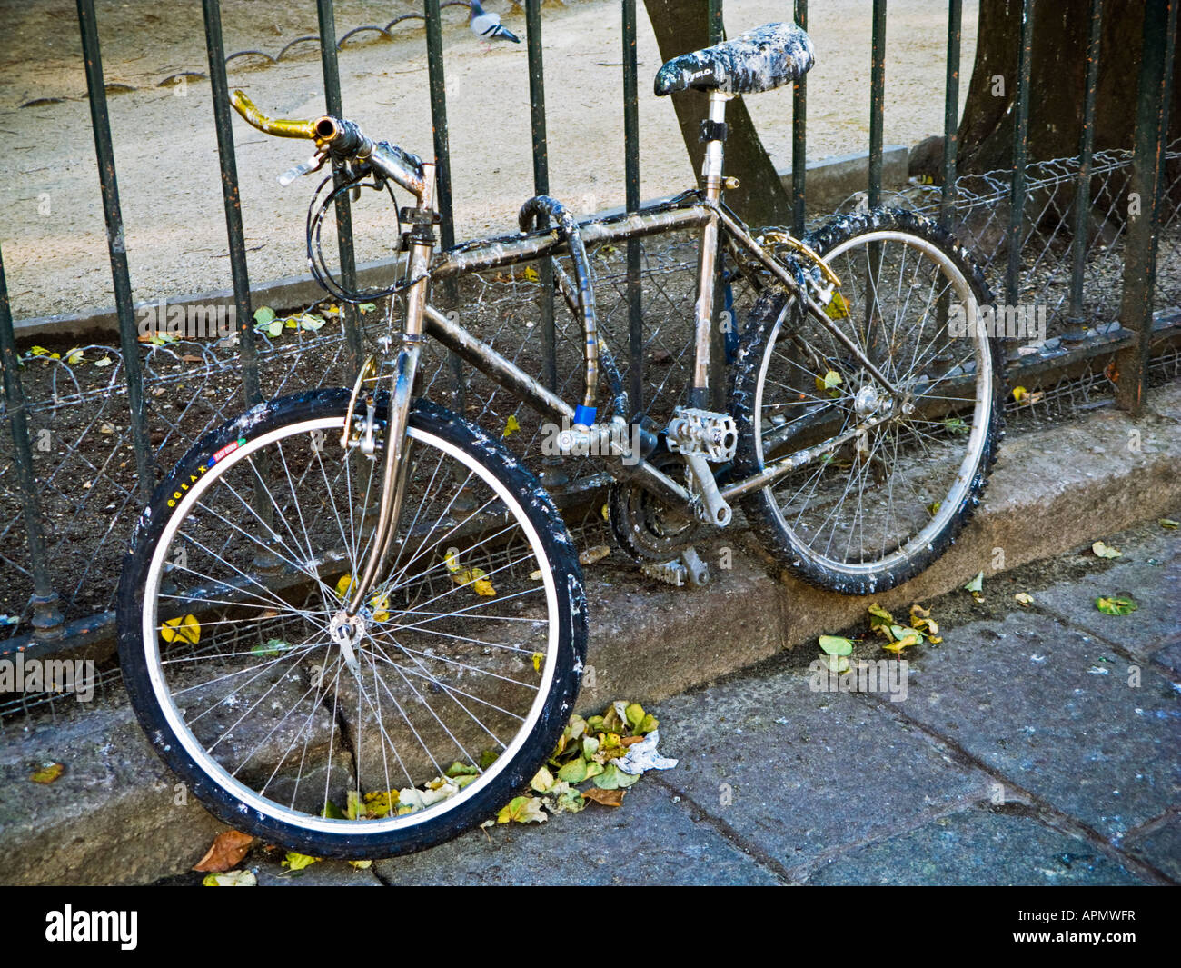Bicycle chained to a fence for a long time is covered in bird droppings Paris France Europe - Stock Image