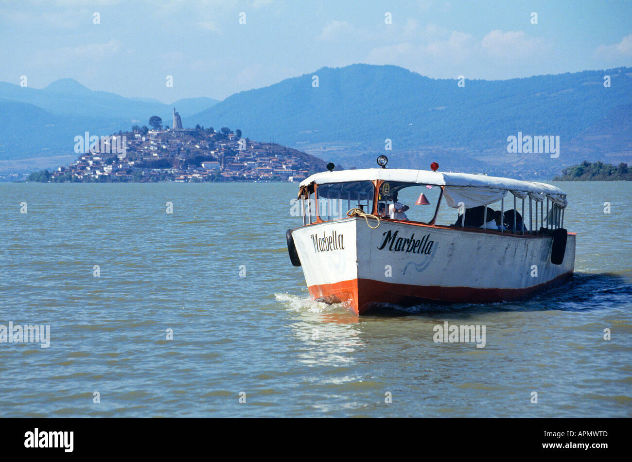 A ferry boat with its name inscribed across the bows leaves behind the Island of Janitzio and surrounding hills in the background as it plies its way through the waters of Lake Patzcuaro - Stock Image