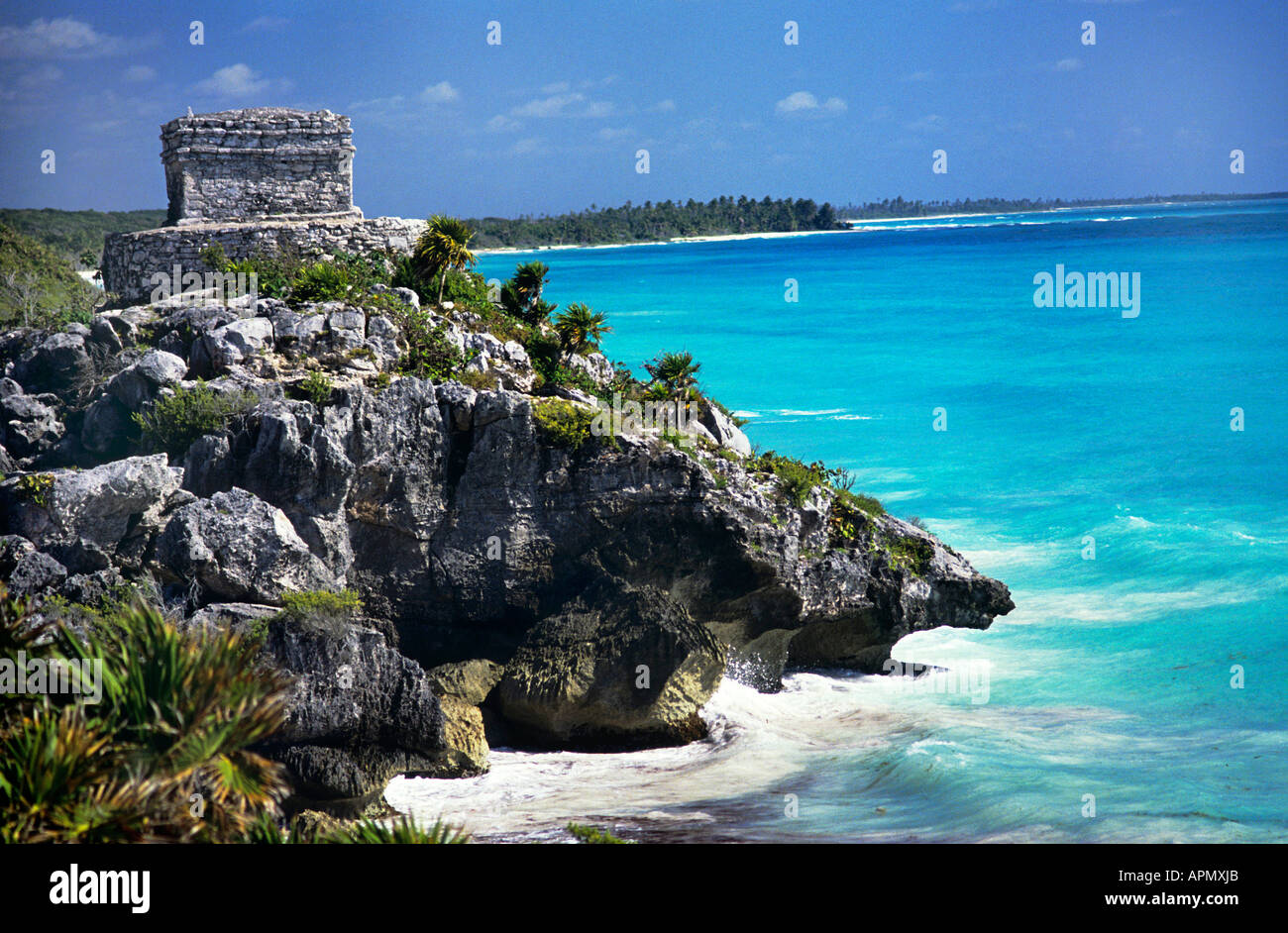 The walled ruins of Tulum settled between AD 900 1500 during the post Classic period set on a craggy cliff overlooking the sparkling turquoise waters of the Caribbean with white capped waves crashing around the rocky coast below - Stock Image