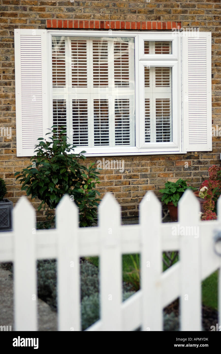 window with interior plantation shutters and exterior shutters with garden and picket fence in foreground - Custom Plantation Shutters