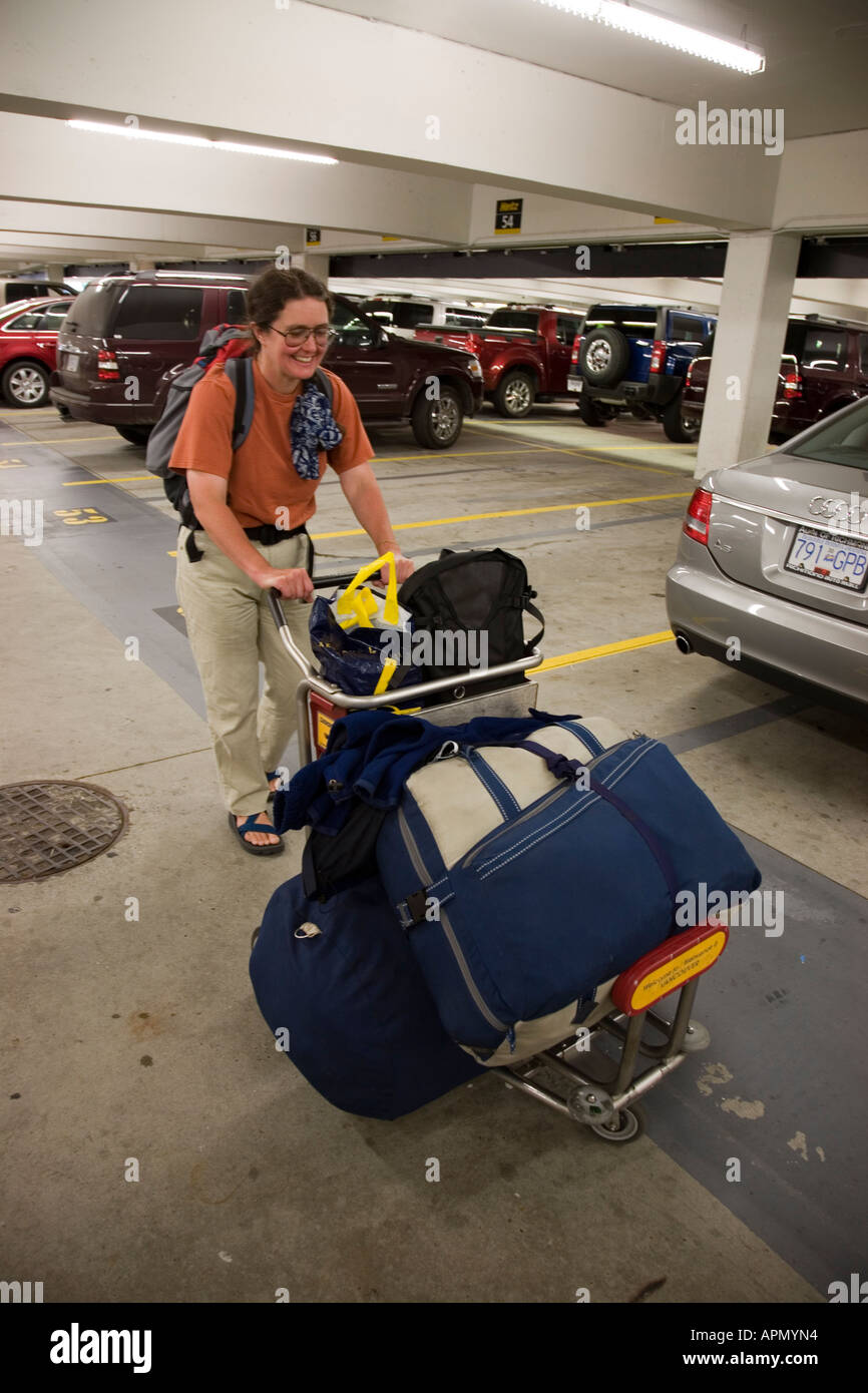 Female Tourist Pushing Airport Trolly Laden With Bags Through Car