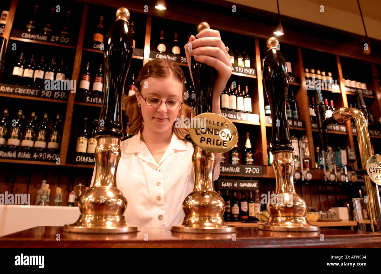 A barmaid serving a traditional British pint of ale in a branch of All Bar One - Stock Image