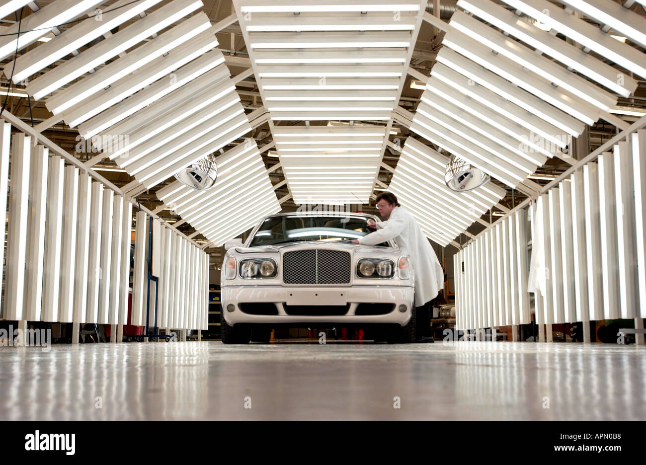 A brand new Bentley gets the finishing touches from a white coated worker - Stock Image