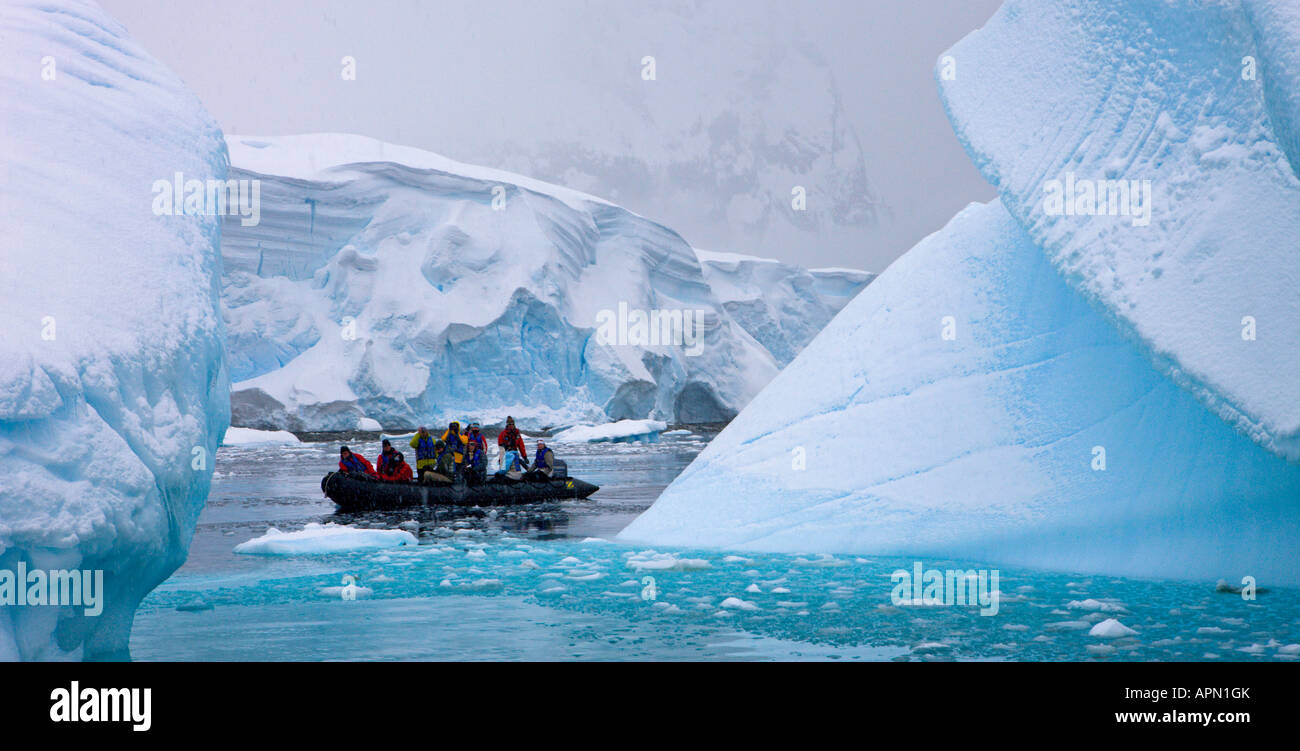 Eco tourists cruise around icebergs in Zodiac boats at Hidden Bay, Antarctica - Stock Image