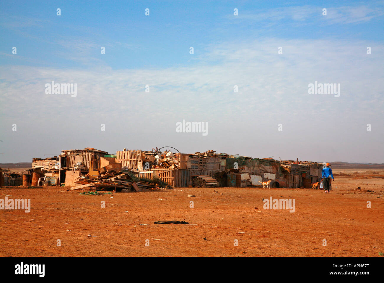 Walking home to the wooden shacks behind the tourist resort of Santa Maria on Sal in the Cape Verde islands - Stock Image