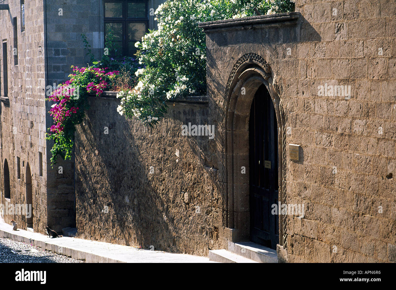 Flowers spilling over the walls framing the arched doorway to the ...