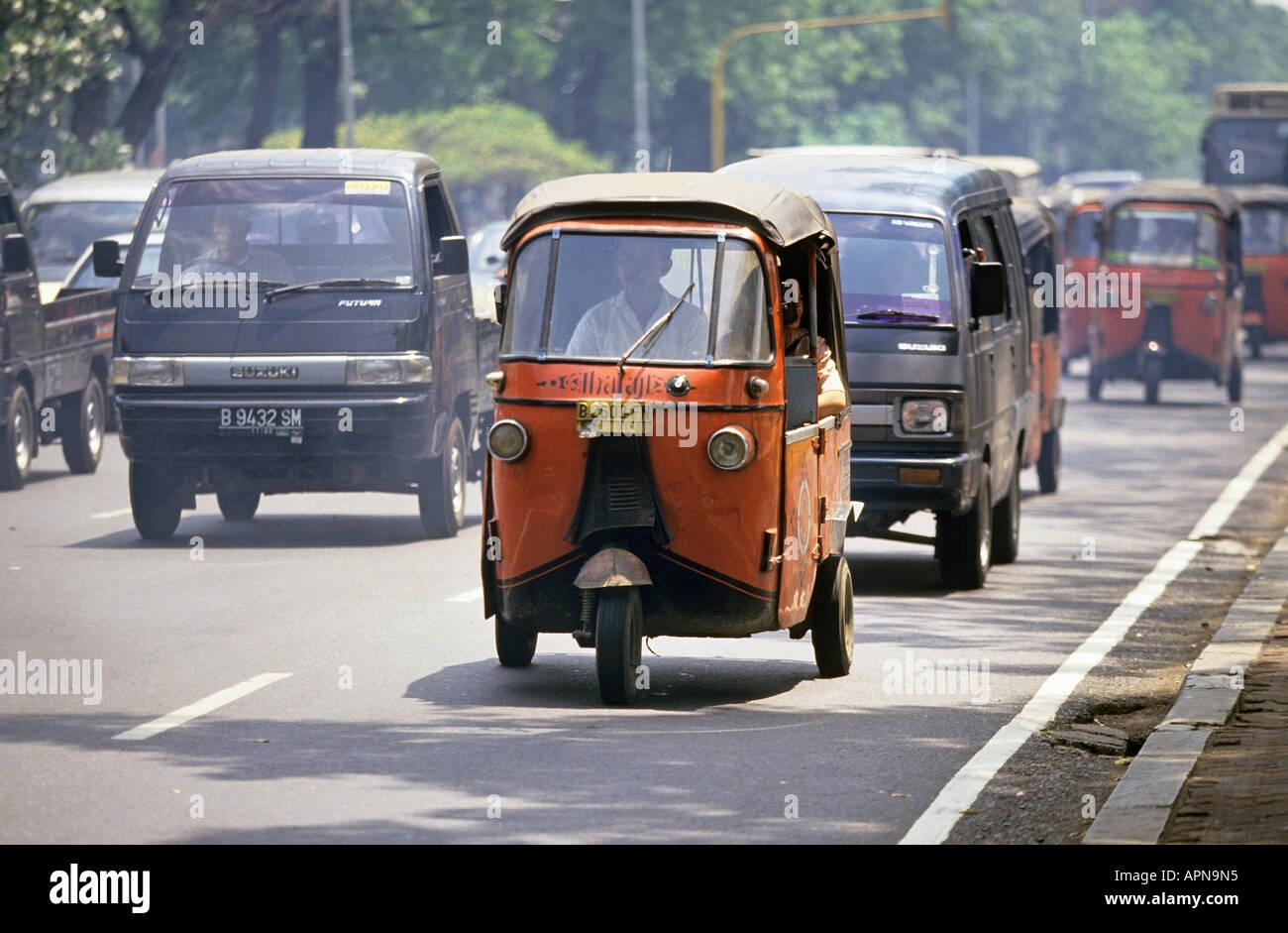 An orange bajaj 3 wheeled motor scooter in traffic on a busy