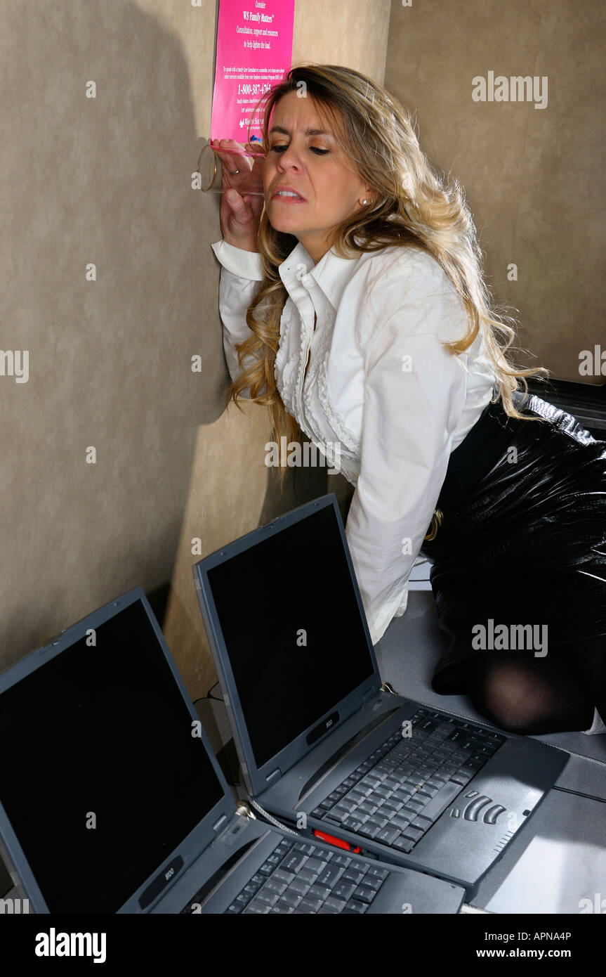 Paranoid female office worker listening through a wall with a glass - Stock Image