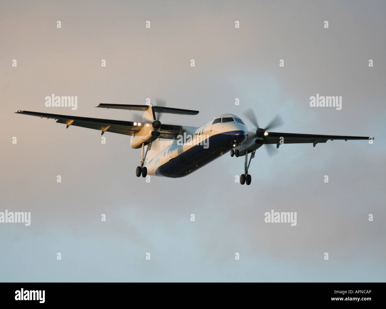 Short haul air travel. Bombardier Dash 8-Q300 twin engine turboprop commuter plane landing at sunset. No airline - Stock Image
