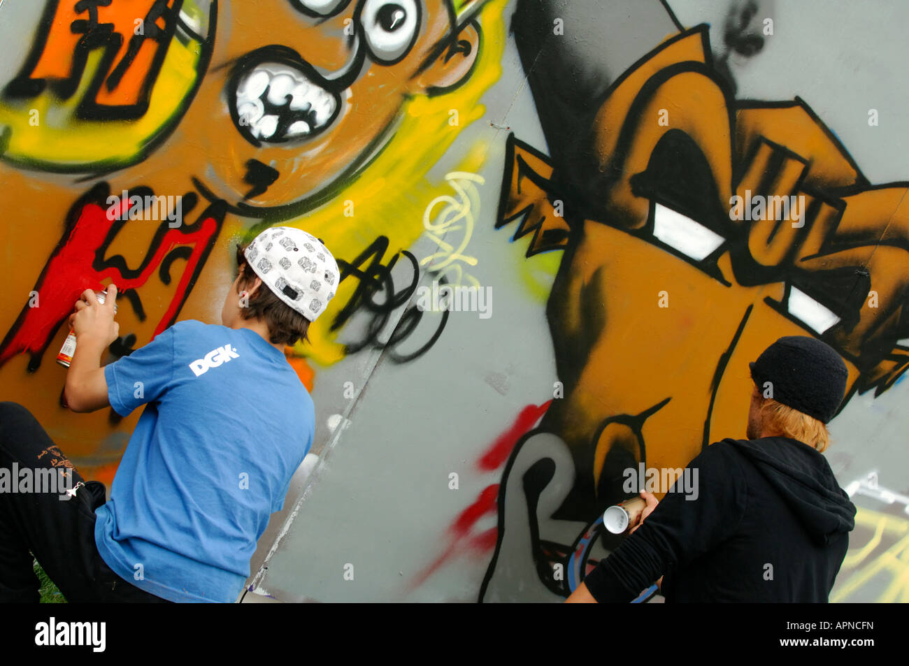 two kids youngsters youths graffitti writing on a wall with spray paints in various colours vandalism criminal damage - Stock Image