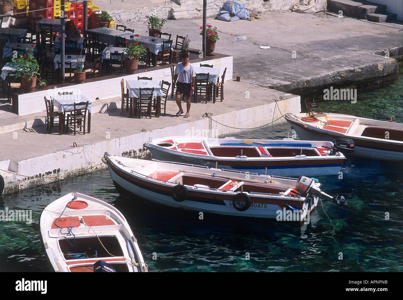 Small motor boats tied up to the waterfront beside the tables and chairs of a small taverna in the coastal village - Stock Image