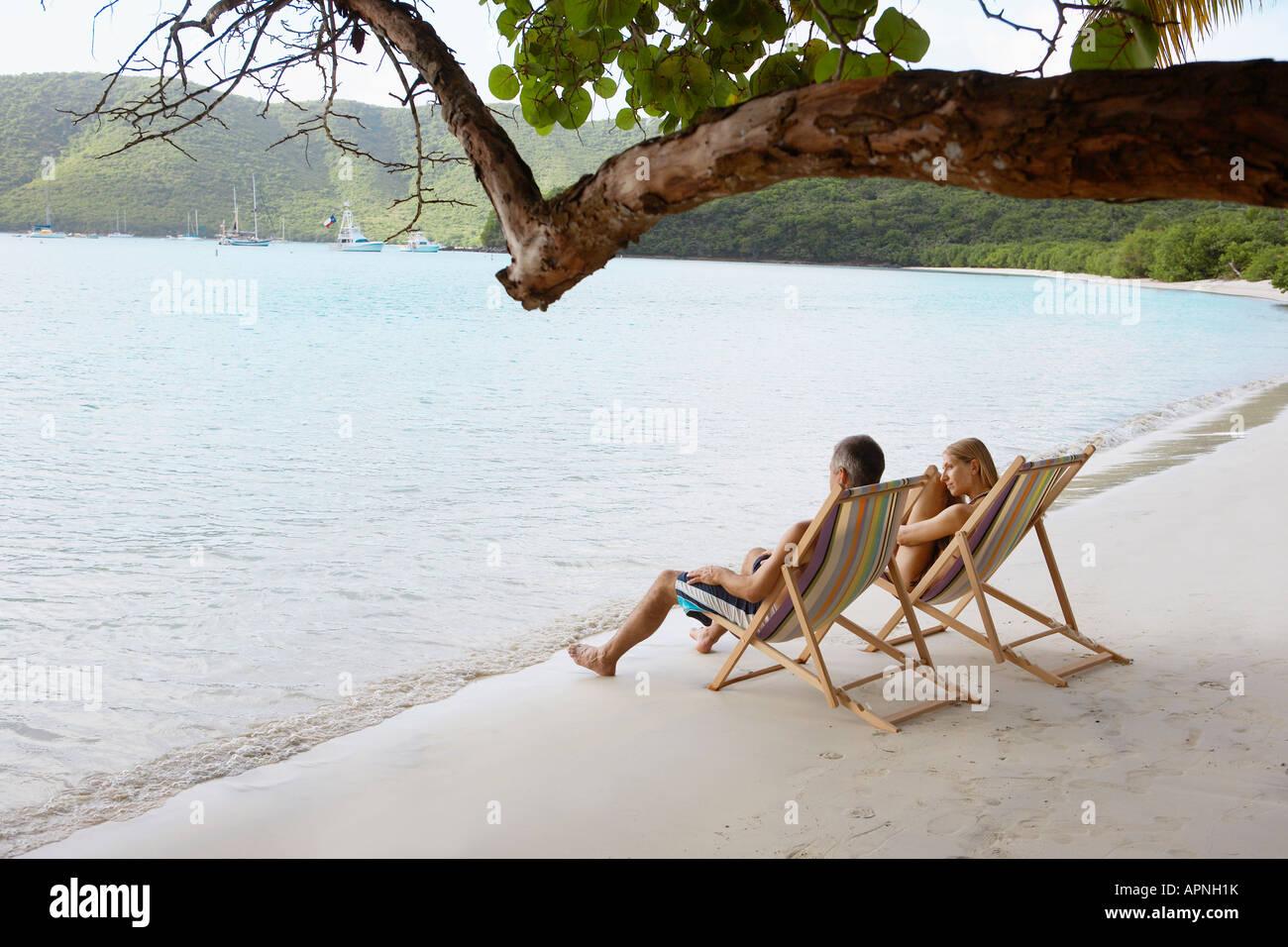 Mid adult couple on lounge chairs on beach (high angle view), St. John, US Virgin Islands, USA Stock Photo