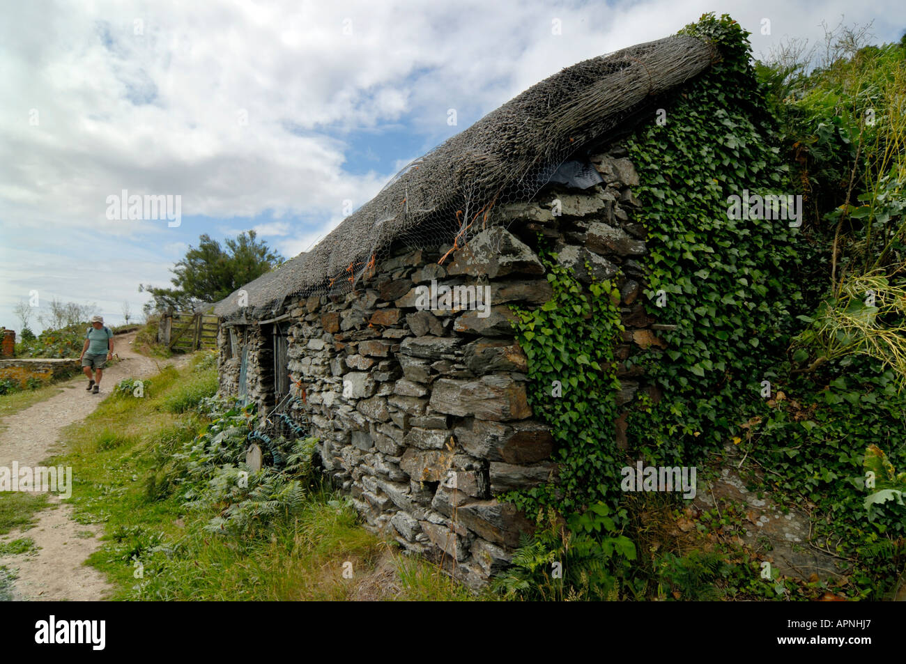 Fishermen's hut at Prusia Cove Prussia Cove Cornwall England and a man walking the Coastal Path - Stock Image