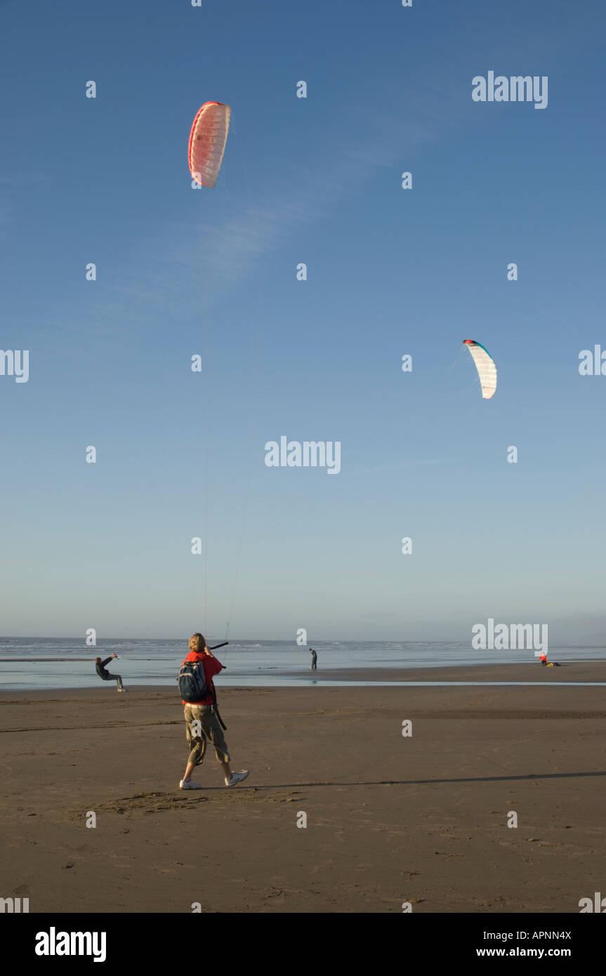 people Powerkite kite flying Ynyslas Borth beach west wales clare blue sky winter January afternoon, UK - Stock Image