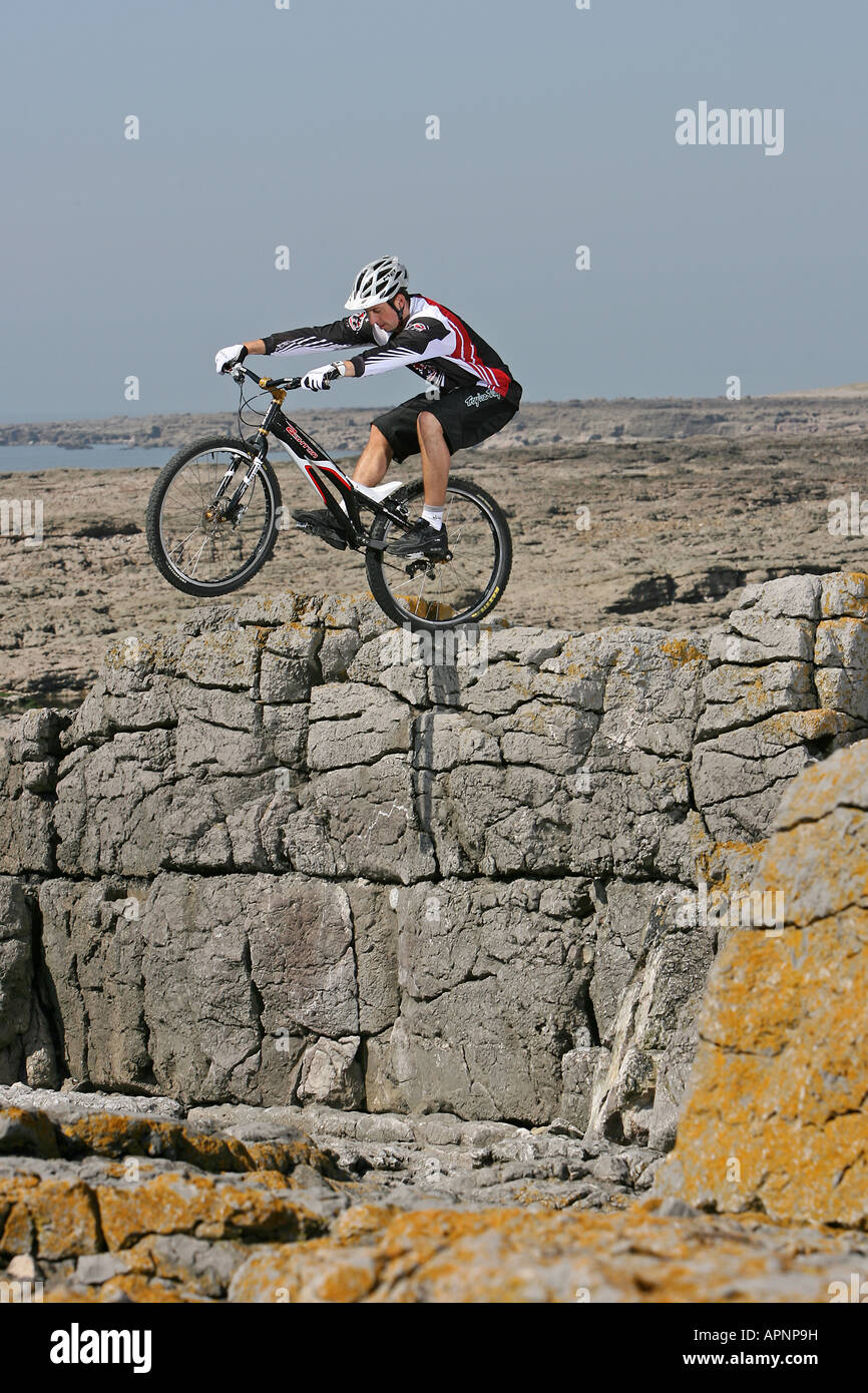 A Mountain Biker perfoms a stunt on some rocks. - Stock Image