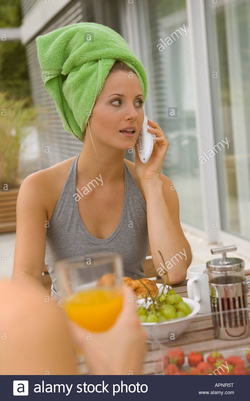 Woman phoning at breakfast table - Stock Image